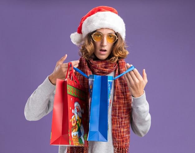 Młody mężczyzna ubrany w świąteczny kapelusz i żółte okulary z ciepłym szalikiem na szyi otwierający świąteczne papierowe torby z prezentami zaskoczony stojąc nad fioletową ścianą