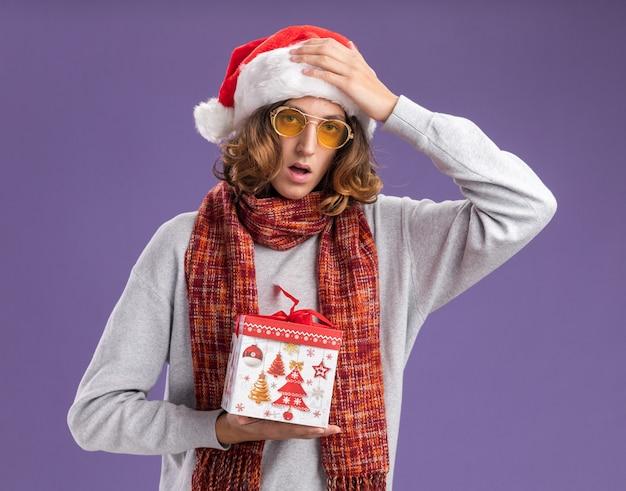 Młody mężczyzna ubrany w świąteczny kapelusz i żółte okulary z ciepłym szalikiem na szyi trzymający prezent świąteczny mylony z ręką nad głową stojącą nad fioletową ścianą
