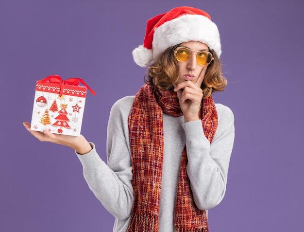 Młody mężczyzna ubrany w świąteczny kapelusz i żółte okulary z ciepłym szalikiem na szyi trzymający prezent świąteczny patrzący w górę z zamyślonym wyrazem myśli stojącym nad fioletową ścianą