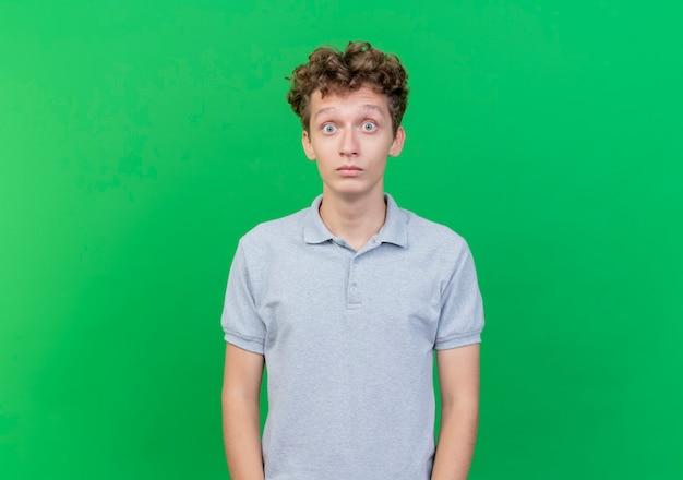 Młody mężczyzna ubrany w szarą koszulkę polo zaskoczony i zdziwiony szeroko otwartymi oczami stojąc nad zieloną ścianą