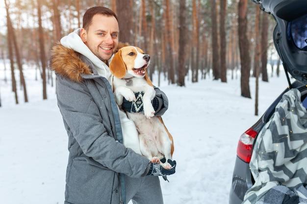 Młody mężczyzna ubrany w szary zimowy park w śnieżnym zimowym lesie trzyma psa o imieniu beagle.