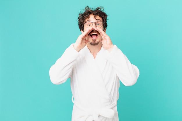 Młody mężczyzna ubrany w szlafrok czuje się szczęśliwy, wydając wielki okrzyk z rękami przy ustach