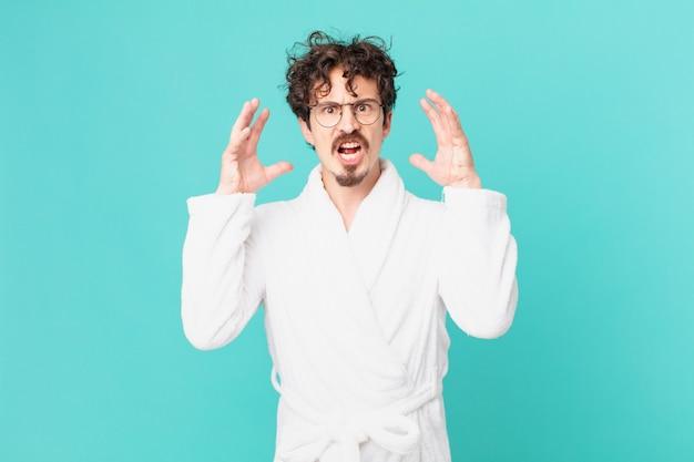 Młody mężczyzna ubrany w szlafrok krzyczy z rękami w górze