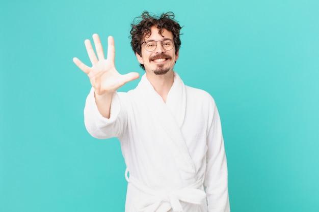 Młody mężczyzna ubrany w szlafrok uśmiechający się i wyglądający przyjaźnie, pokazujący numer pięć