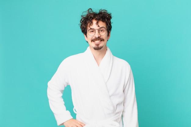 Młody mężczyzna ubrany w szlafrok, uśmiechający się radośnie z ręką na biodrze i pewny siebie