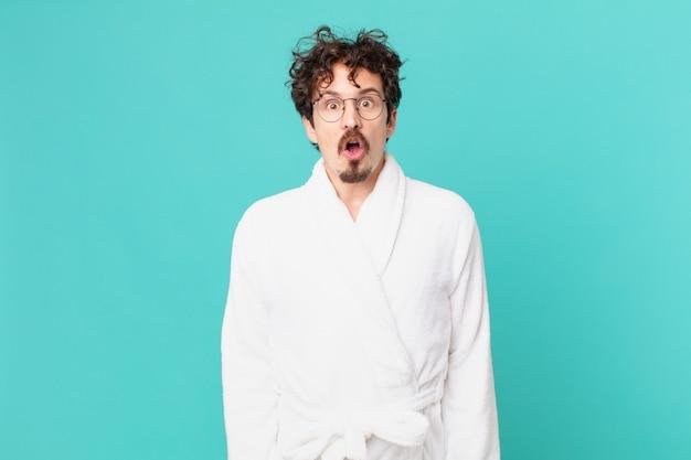 Młody mężczyzna ubrany w szlafrok wyglądający na bardzo zszokowanego lub zdziwionego