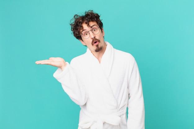 Młody mężczyzna ubrany w szlafrok, wyglądający na zaskoczonego i zszokowanego, z opuszczoną szczęką, trzymający przedmiot