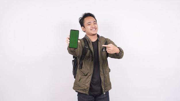 Młody mężczyzna ubrany w torbę na białym tle wskazał zielonego telefonu
