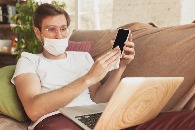 Młody mężczyzna uczący się w domu podczas kursów online dla dezynfektora, pielęgniarki, usług medycznych.