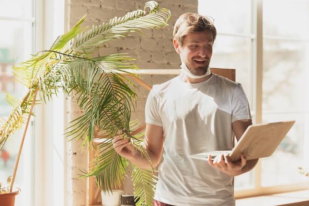 Młody mężczyzna uczący się w domu podczas kursów online dla ogrodnika, biologa, kwiaciarza. zdobywanie zawodu w izolacji, kwarantanna przeciwko rozprzestrzenianiu się koronawirusa. korzystanie z laptopa, smartfona, słuchawek.