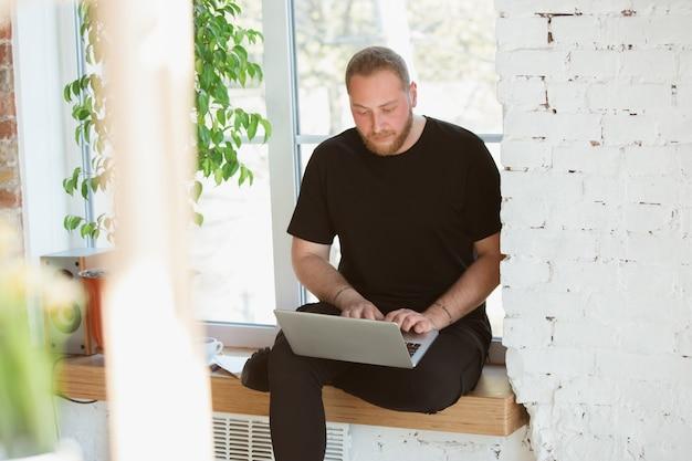 Młody mężczyzna uczący się w domu podczas kursów online