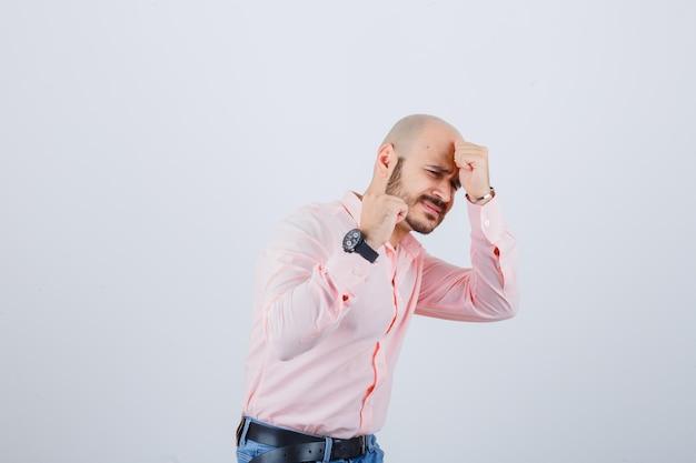 Młody mężczyzna udając, że broni się w koszuli, dżinsach i patrząc przestraszony, widok z przodu.