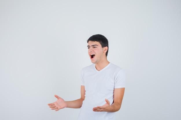 Młody mężczyzna udając, że pokazuje coś w koszulce i patrząc wesoło, widok z przodu.
