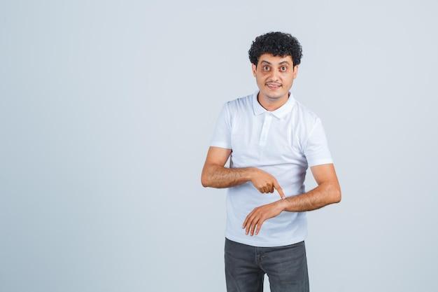 Młody mężczyzna udając, że wskazuje palcem wskazującym do zegara w białej koszulce i dżinsach i wygląda optymistycznie, widok z przodu.