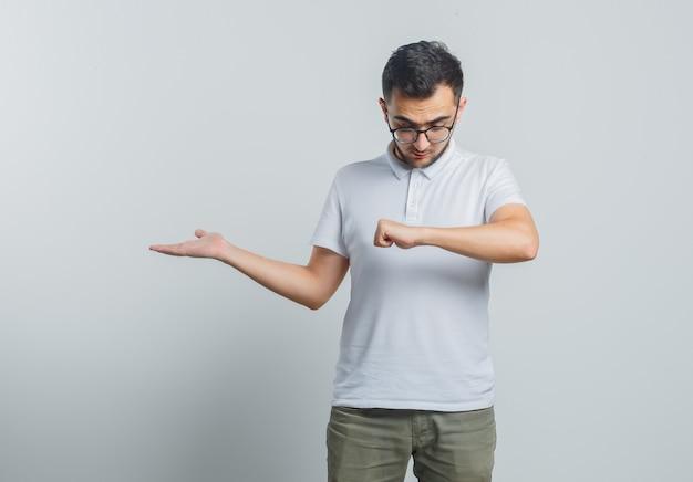 Młody mężczyzna udający, że patrzy na zegarek na nadgarstku, pokazujący coś w białej koszulce, spodniach i wyglądający na skupionego