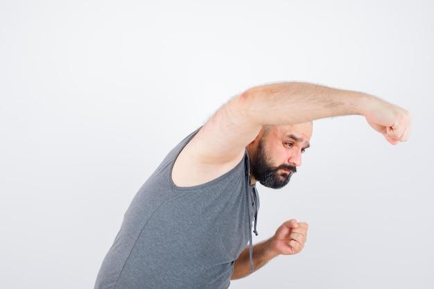 Młody mężczyzna udaje, że uderza pięścią w bluzę bez rękawów i wygląda na złośliwego. przedni widok.
