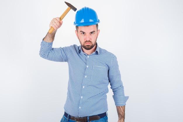 Młody mężczyzna uderza w głowę młotkiem w koszuli, dżinsach, kasku i wygląda głupio, widok z przodu.
