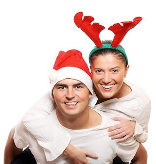 Młody mężczyzna ujeżdżający kobietę na barana, obaj w strojach świątecznych