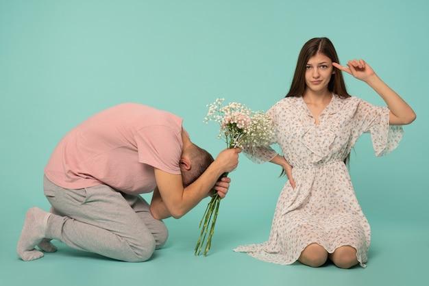 Młody mężczyzna ukląkł w pozie niewolnika i trzymał wiosenne kwiaty