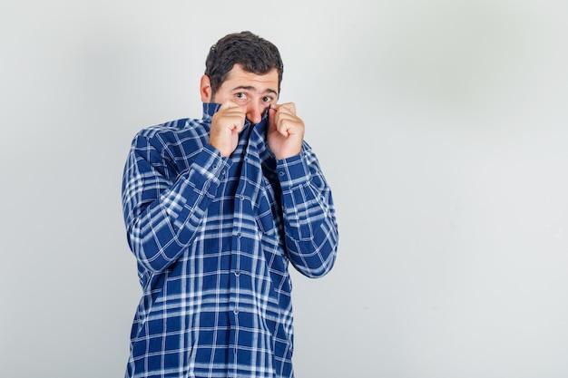 Młody mężczyzna ukrywa twarz za kołnierzem w kraciastej koszuli i wygląda na przestraszonego.