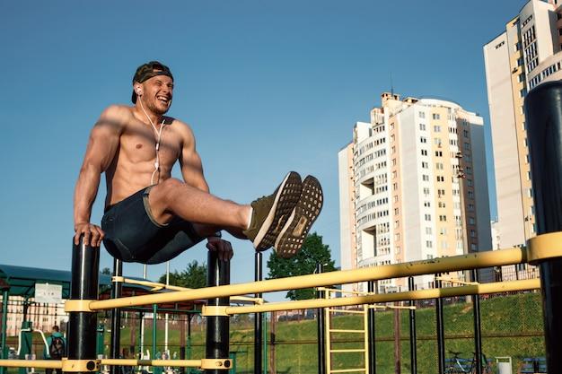 Młody mężczyzna unosi nogi na boisku sportowym, sportowiec, trening na świeżym powietrzu w mieście, ćwiczenia prasowe