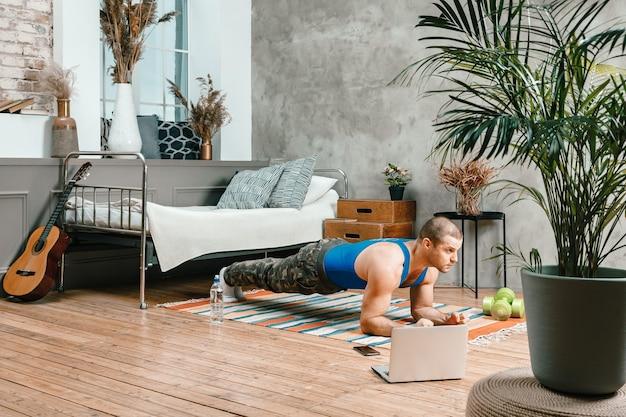 Młody mężczyzna uprawia sport w domu i ogląda trening online z laptopa w sypialni