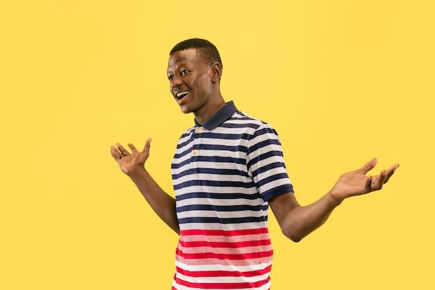 Młody mężczyzna uśmiecha się na białym tle na żółtej ścianie