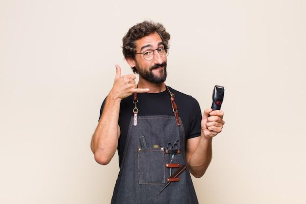 Młody mężczyzna uśmiecha się radośnie, dzwoniąc do ciebie później gestem, rozmawiając przez telefon