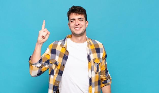 Młody mężczyzna uśmiecha się radośnie i radośnie, wskazując jedną ręką w górę, aby skopiować przestrzeń