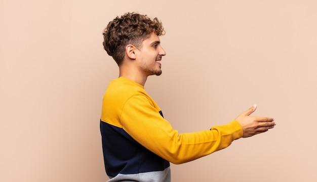 Młody mężczyzna uśmiecha się, wita i oferuje uścisk dłoni, aby zamknąć udaną transakcję, koncepcja współpracy