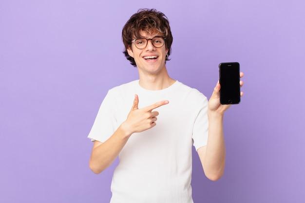 Młody mężczyzna uśmiechający się radośnie, czujący się szczęśliwy, wskazujący na bok i trzymający komórkę
