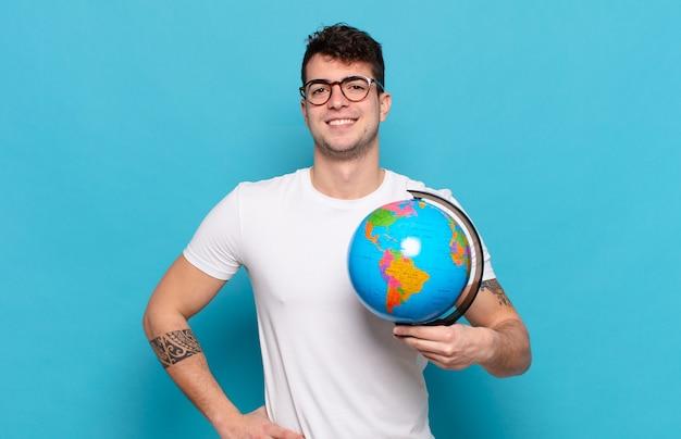 Młody mężczyzna uśmiechający się radośnie z ręką na biodrze i pewny siebie, pozytywny, dumny i przyjazny