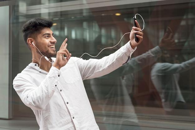Młody mężczyzna uśmiechający się zadowolony podczas rozmowy wideo przy użyciu smartfona w mieście