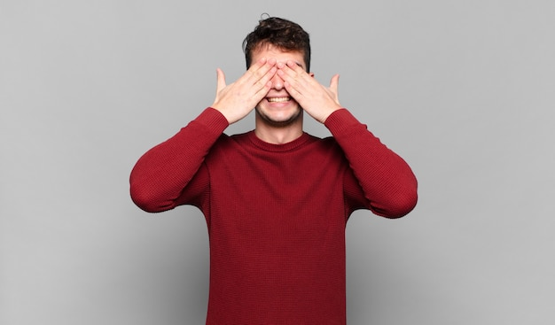 Młody mężczyzna uśmiechnięty i szczęśliwy, zakrywający oczy obiema rękami i czekający na niewiarygodną niespodziankę