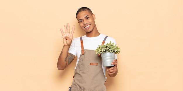 Młody mężczyzna uśmiechnięty i wyglądający przyjaźnie, pokazujący cyfrę cztery lub czwartą z ręką do przodu, odliczający w dół