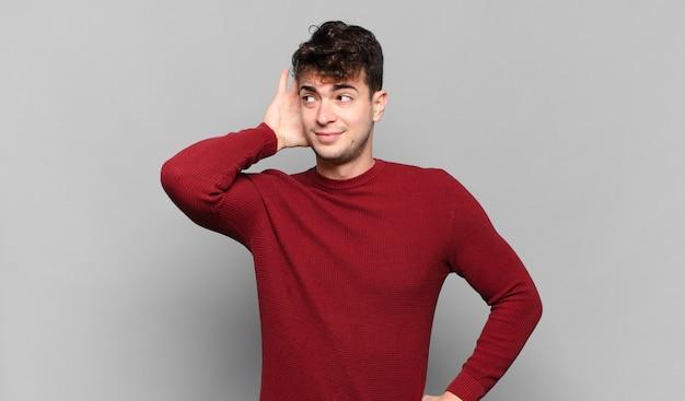 Młody mężczyzna uśmiechnięty, z zaciekawieniem spoglądający w bok, usiłujący wysłuchać plotek lub podsłuchać jakąś tajemnicę
