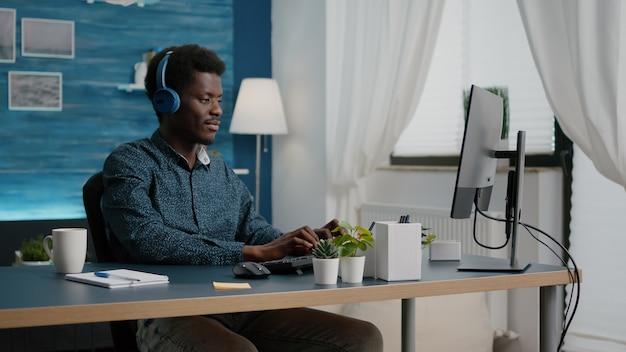 Młody mężczyzna używa słuchawek do słuchania muzyki podczas pracy w domowym biurze na komputerze