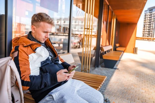 Młody mężczyzna używa smartfona siedząc na przystanku autobusowym biznesmen czeka na autobus