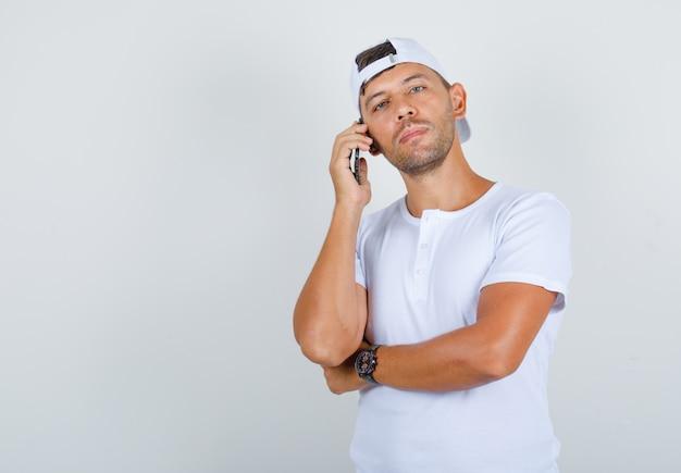 Młody mężczyzna w białej koszulce, czapce trzymając telefon i patrząc na kamery, widok z przodu.