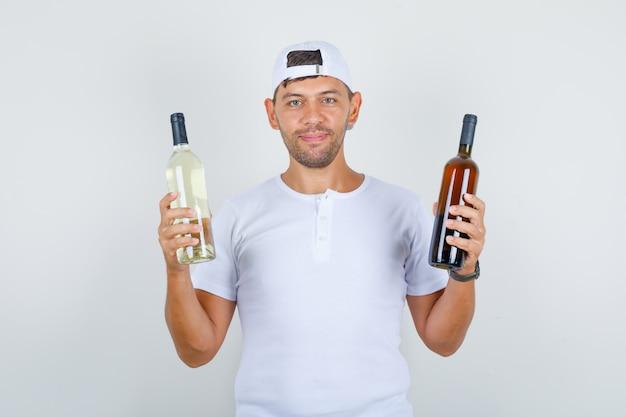 Młody mężczyzna w białej koszulce, czapce trzymającej butelki napojów alkoholowych i patrząc szczęśliwy, widok z przodu.