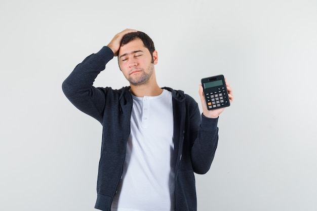 Młody mężczyzna w białej koszulce i czarnej bluzie z kapturem na suwak, trzymając kalkulator, kładąc rękę na głowie i patrząc optymistycznie z przodu.
