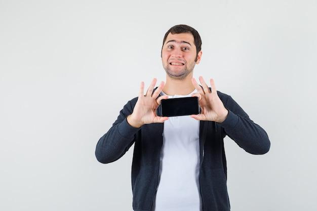 Młody mężczyzna w białej koszulce i czarnej bluzie z kapturem na suwak, trzymając smartfon obiema rękami i wyglądający na szczęśliwego, widok z przodu.