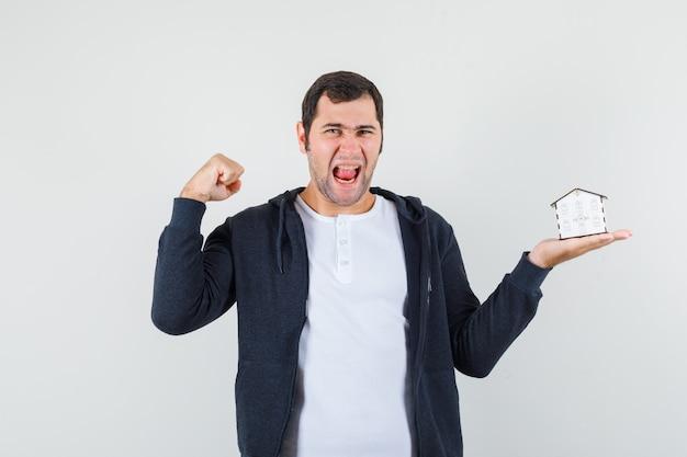Młody mężczyzna w białej koszulce i czarnej bluzie z kapturem na suwak, trzymając w jednej ręce model domu, pokazujący mięśnie i wyglądający optymistycznie, widok z przodu.
