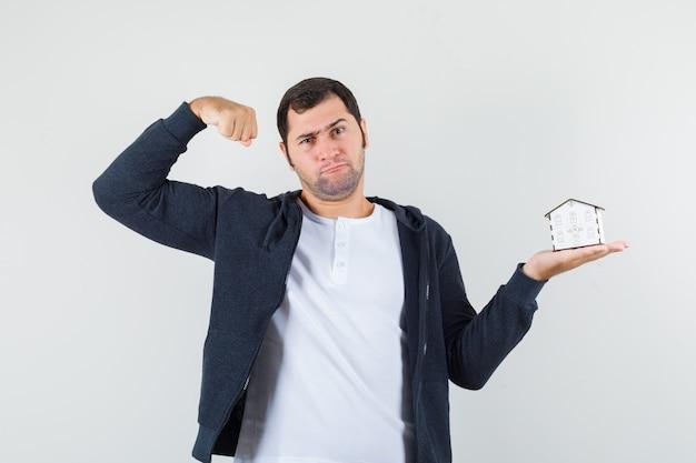 Młody mężczyzna w białej koszulce i czarnej bluzie z kapturem na suwak, trzymając w jednej ręce model domu, pokazujący mięśnie i wyglądający poważnie, widok z przodu.