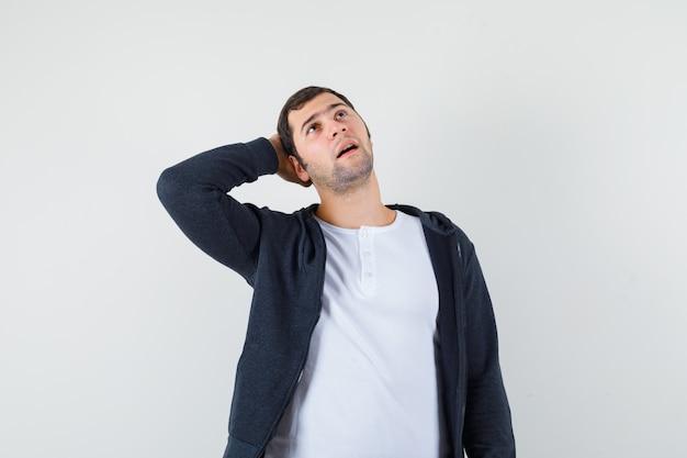 Młody mężczyzna w białej koszulce i czarnej bluzie zapinanej na suwak, kładąc rękę za głową, myśląc o czymś i patrząc optymistycznie z przodu.