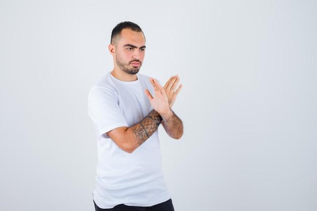 Młody mężczyzna w białej koszulce i czarnych spodniach pokazujący gest x i wyglądający poważnie