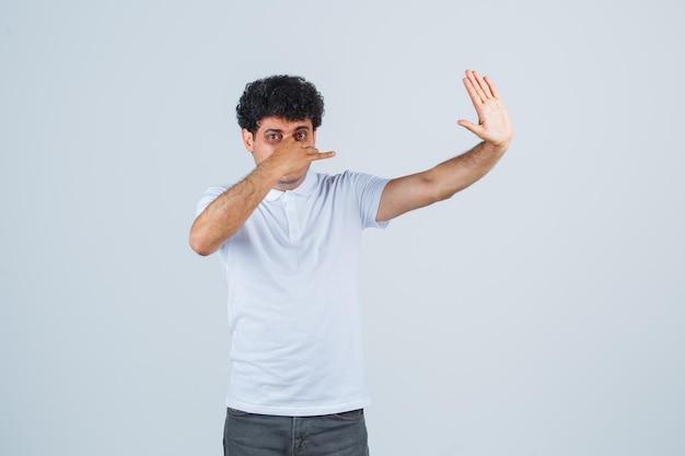 Młody mężczyzna w białej koszulce i dżinsach szczypie nos z powodu nieprzyjemnego zapachu, pokazuje znak stopu i wygląda na zmęczonego, widok z przodu.