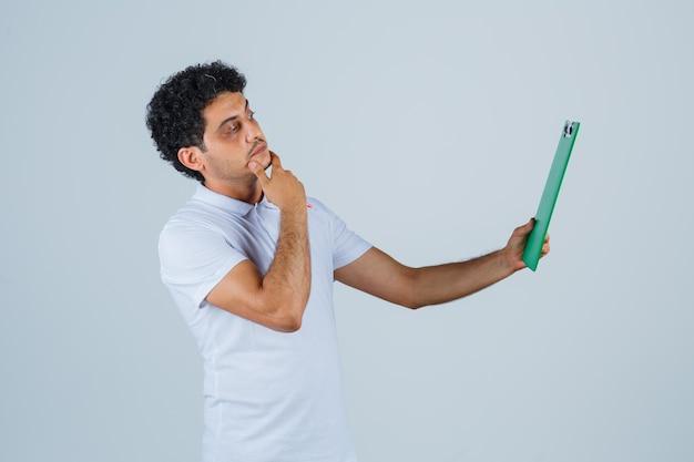 Młody mężczyzna w białej koszulce i dżinsach, trzymając notatnik i długopis, patrząc na notatnik i patrząc zamyślony, widok z przodu.