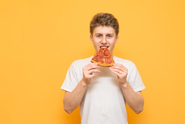 Młody mężczyzna w białej koszulce i kawałku pizzy jest izolowany na żółto
