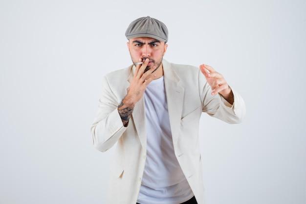 Młody mężczyzna w białej koszulce, kurtce i szarej czapce palący papierosy i wyciągający rękę do przodu i wyglądający na zły